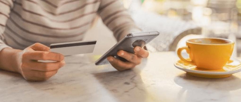 Mujer revisando celular y tarjeta de crédito